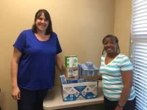 ARC Program Director Heather Gisczinski and Administrative Assistant Marcilla Dale receive a donation of CFL bulbs from Baldwin EMC.