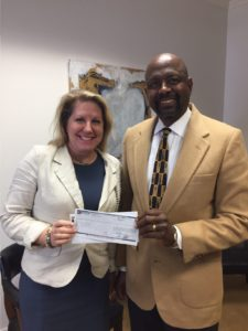 Baldwin EMC District 3 Trustee Aubury Fuller (right) presents Baldwin EMCs tax payment to Fairhope Mayor Karin Wilson.